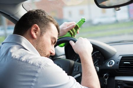 Drunk man driving car and falling asleep at the wheel