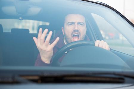Rude man rijdt zijn auto en richt veel op