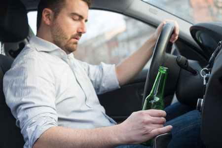 wine road: Drunk man driving car and falling asleep at the wheel