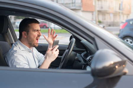 Rude man driving his car and talking on mobile phone Stock Photo