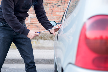 disarm: Thief trying to pick the lock of a parked car