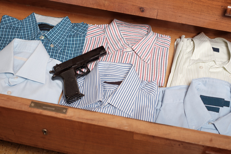 Gun hidden in a drawer full of shirt at home Stock Photo