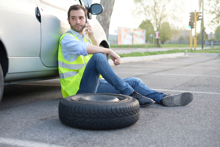 Man calling help service for a flat tyre after vehicle breakdown