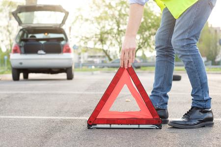 車の故障後反射赤色の三角形を配置する男