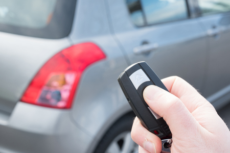 Hand holding a car alarm key with anti-theft
