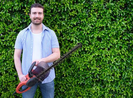 Hobbyist  gardner  using an hedge clipper in his home garden