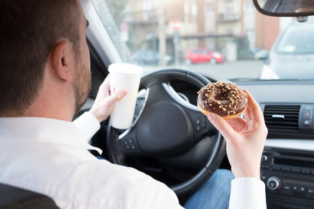 Man met ontbijt en rijden in zijn auto