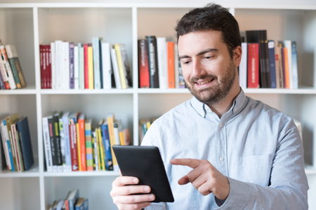 Man holding an e-book reader in hands Stock Photo