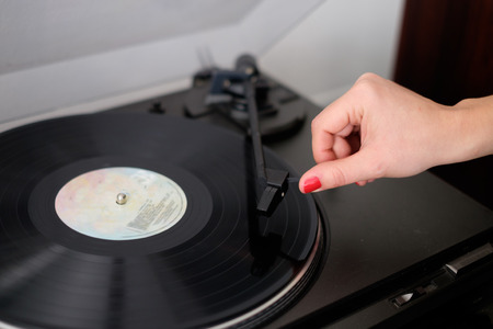 counterweight: Woman listening to music using vintage vinyl record