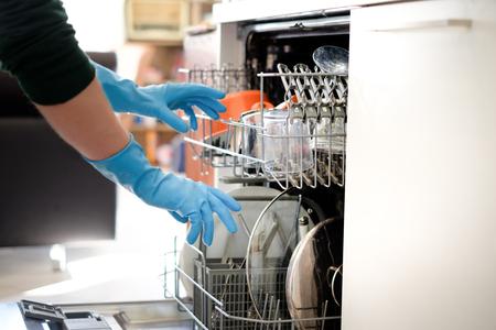 女性メインのキッチンで食器洗い機を開いてお皿に焦点を当てる