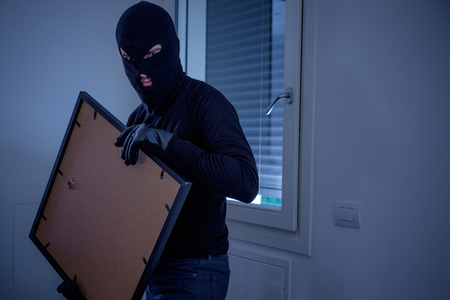 Thief inside home  stealing a painting from the wall