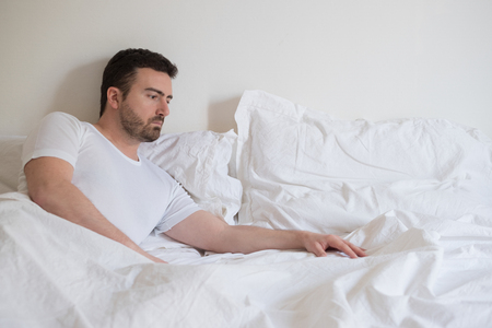 Sad and upset man waking up alone in the morning light Stock Photo