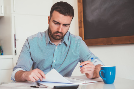 Man calculating bills and tax expenses