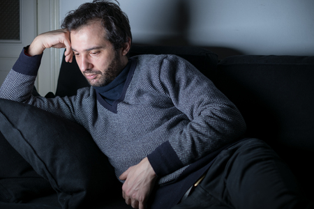 daybreak: Man tired and depressed lying on the couch Stock Photo