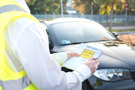 Police officer giving a ticket fine for parking violation Stock Photo