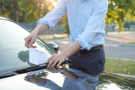 law breaker: Man finding a ticket fine because of parking violation
