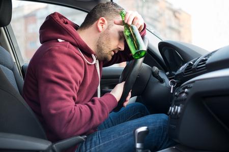 술에 취해 남자가 차를 운전하고 휠에서 잠들다
