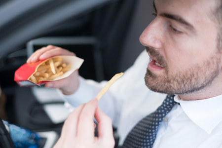 Man eating junk food and driving seated in his car