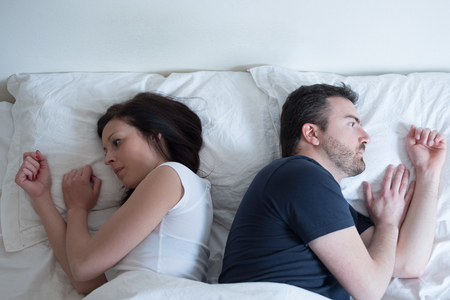 Sad and thoughtful couple after arguing lying in the bed