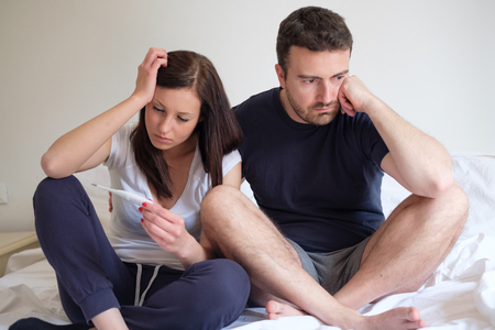 two people fertility: Sad lovers couple after a pregnancy test result