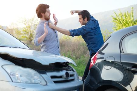 Dos hombres enojados discutiendo después de un accidente de coche fender-bender Foto de archivo