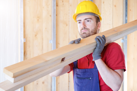 Carpenter worker holding wooden boards Stock Photo