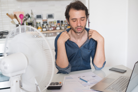 Sweaty man trying to refresh from heat with a fan