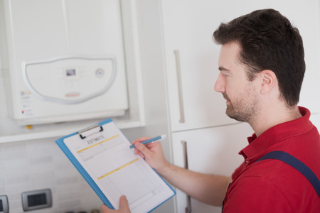 Plumber making a control check on the home water boiler