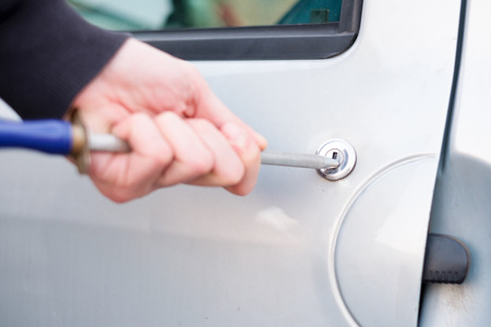 tool unlock: Thief trying to pick the lock of a parked car