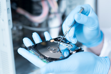 information analysis: Lab engineer repairing and fixing broken hard disk for data recovery