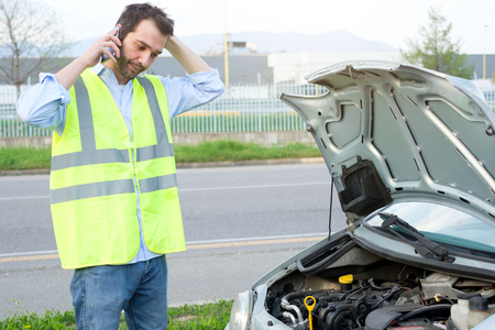 Upset man calling assistance mechanic service after car breakdown Stock Photo