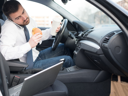 Man eating an hamburger and working seated in his car