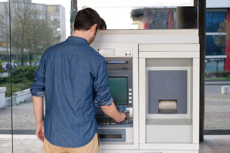 Man met zijn credit card in een ATM voor geldopname Stockfoto