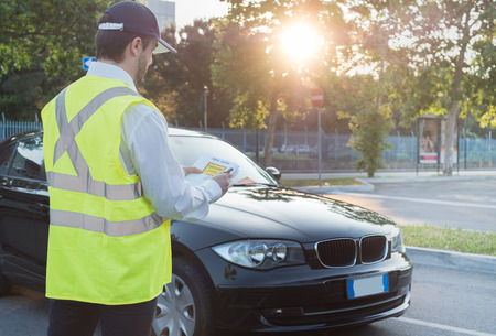 Police officer giving a ticket fine for parking violation Stockfoto