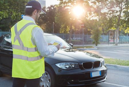 Police officer giving a ticket fine for parking violation Standard-Bild