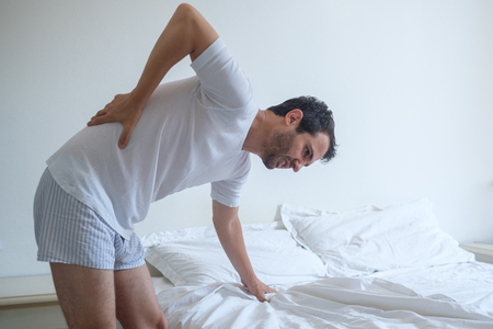 Man feeling back ache in the bed after sleeping Stock fotó