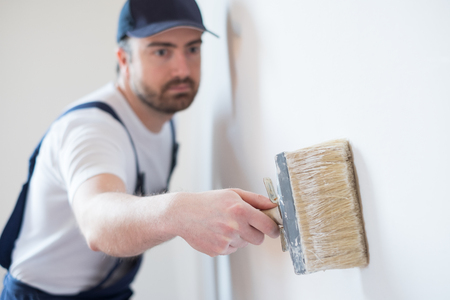 Professional painter worker is painting a wall photo