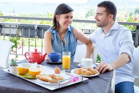 Lovers couple having breakfast in hotel photo