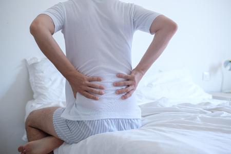 Hombre despertando por la mañana y sufriendo por dolor de espalda Foto de archivo - 83892357