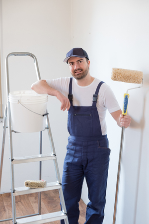 Man ready to paint a wall holding painting tools photo