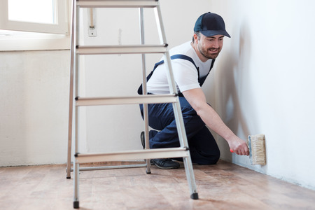 Professional painter worker is painting one wall photo