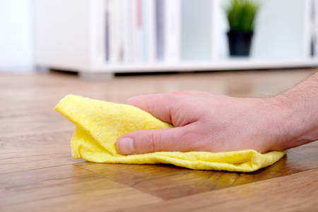 Detail of a hand with sponge cleaning a parquet floor