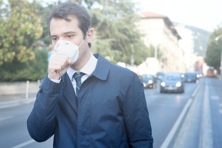 Man walking in the city wearing protection mask against smog air pollution Stockfoto