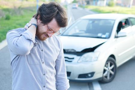 自動車事故の後で首に痛みを感じる男