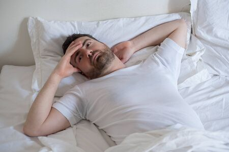Thoughtful man trying to sleep in his bed at night Stock Photo