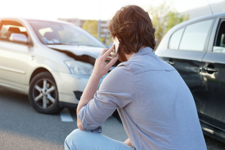 pileup: Man calling help after a car crash accident on the road