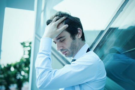 unemployed dismissed: Desperate and stressed businessman feeling bad outside the office.Blue effect added. Stock Photo