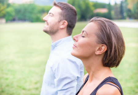 Profile of a couple of man and woman breathing deep fresh air together in the nature Banque d'images