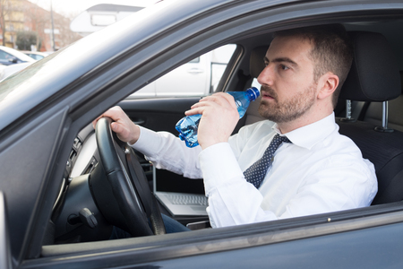 Man drinking water seated in his car