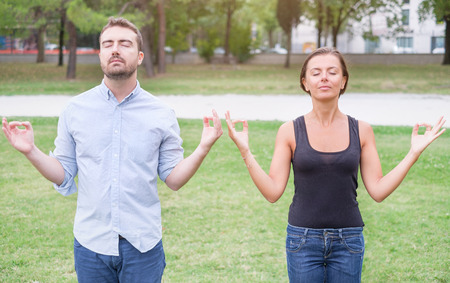 Profile of a couple of man and woman meditating together in the nature